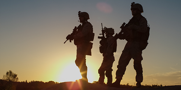 Military personnel in combat gear at sunset