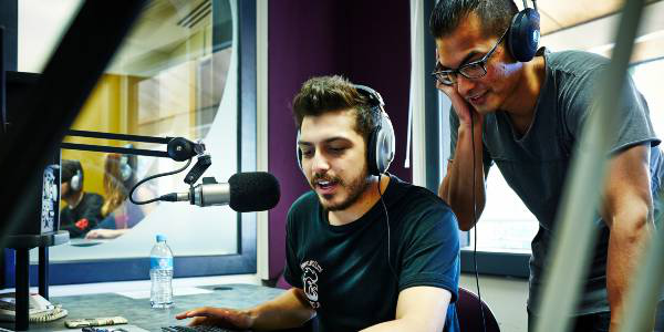 two male students broadcasting in a radio studio