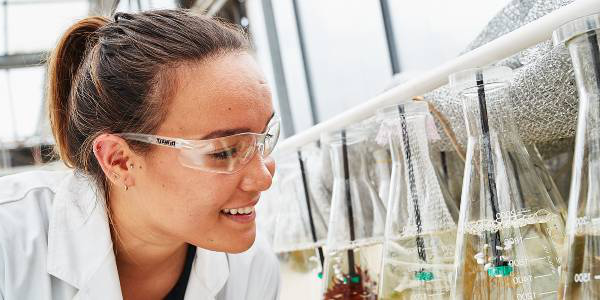 female science student inspecting glass beakers