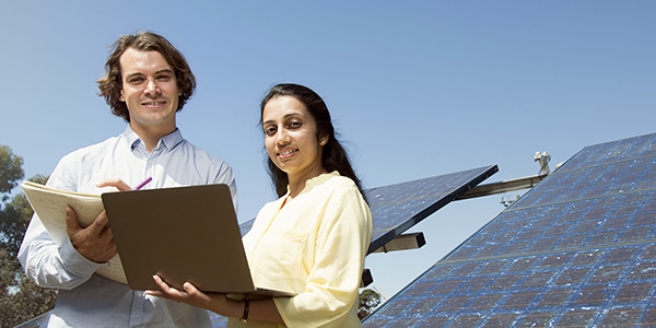 Two students working in front of solar panels