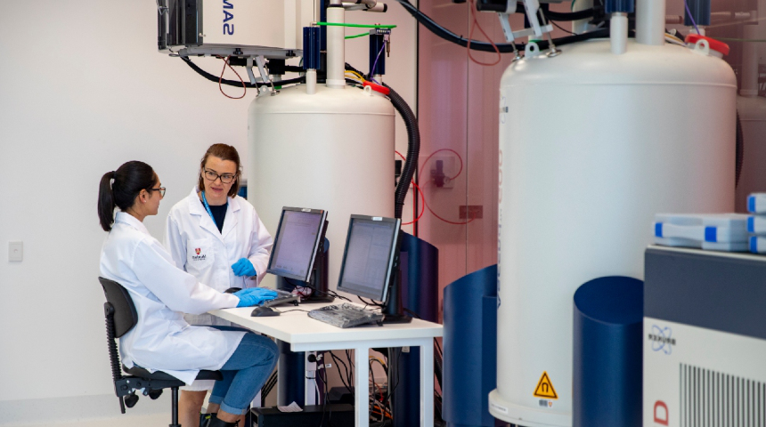 Two female researchers operating at large NMR lab equipment